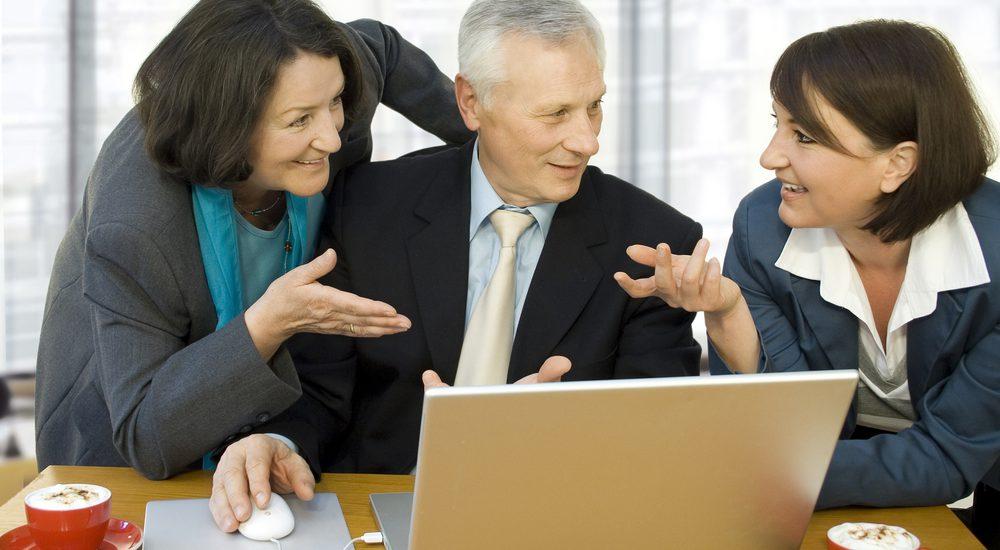 Zwei Senioren und eine junge Frau bei der Arbeit
